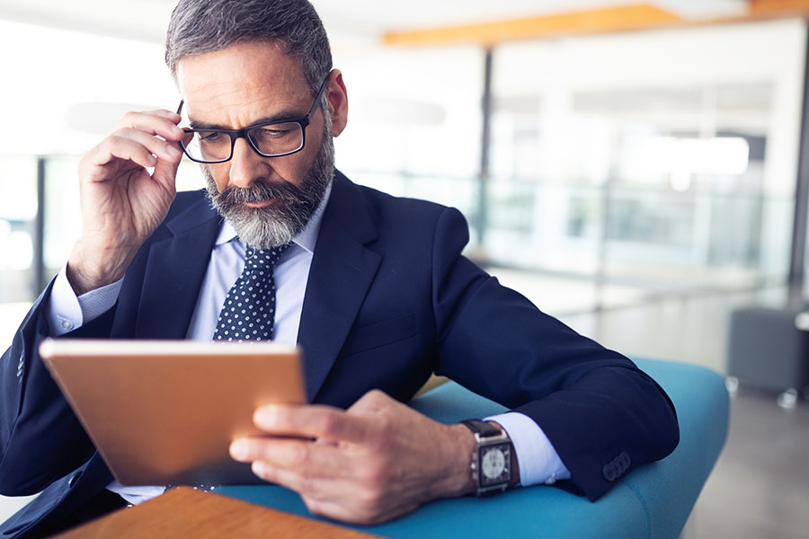 Blog - Businessman Sitting In Modern Office Looking At His Tablet