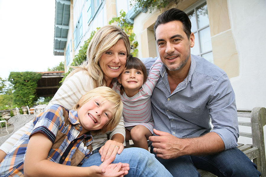 Personal Insurance - Happy Family Of Four Sitting Outside Their Home